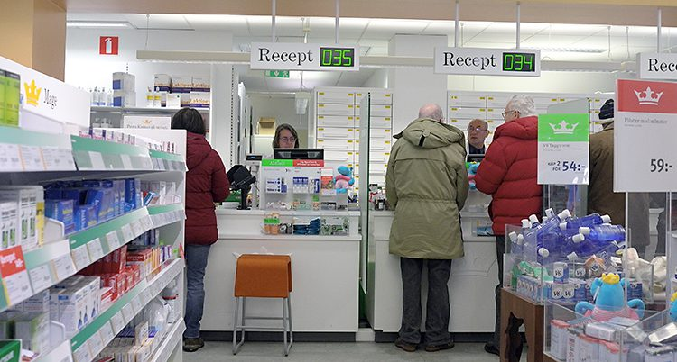 Folk står i kassan på ett apotek.
