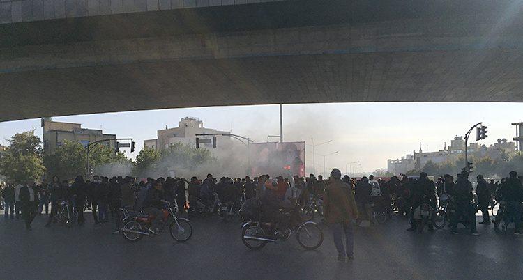 En stor samling med människor i staden Isfahan. Framför folksamlingen kör två personer förbi med mopeder. Bakom folksamlingen syns rök i luften.