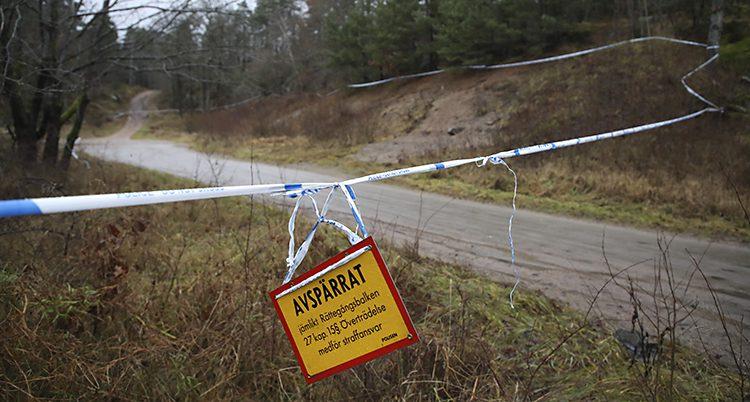 En väg som går in i ett skogsområde. Poliser har satt upp band i blått och vitt som spärrar av området. På bandet hänger en gul skylt där det står Avspärrat.