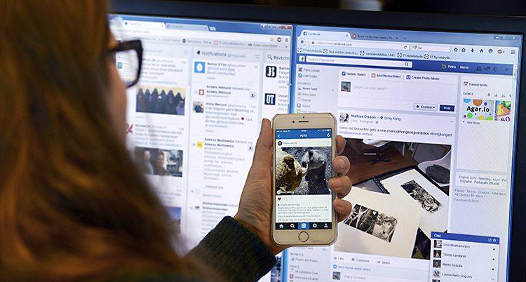 En kvinna sitter framför en dator. I handen håller hon i en mobil. På datorn syns sajten Facebook. Den sajten samlar in mycket information om sina användare.