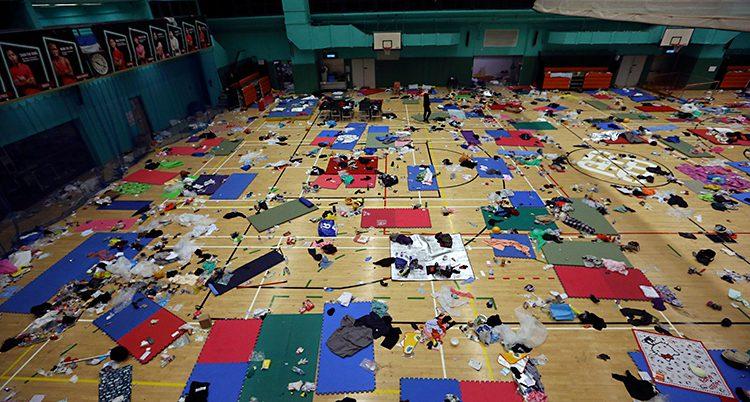 En gymnastiksal som är fotograferad uppifrån. På golvet syns massor av madrasser och andra saker.