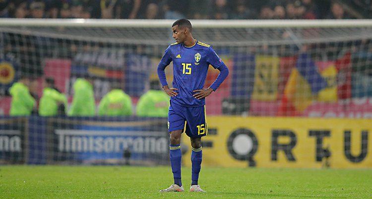 En fotbollsplan. Mitt i bilden står spelaren Alexander Isak. Han har Sveriges blå dräkt på sig. I bakgrunden syns ett fotbollsmål och publik.