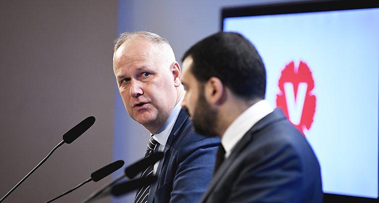 Vänsterpartiets ledare Jonas Sjöstedt och Ali Esbati. De har mikrofoner framför sig. I bakgrunden syns Vänsterpartiets logga.