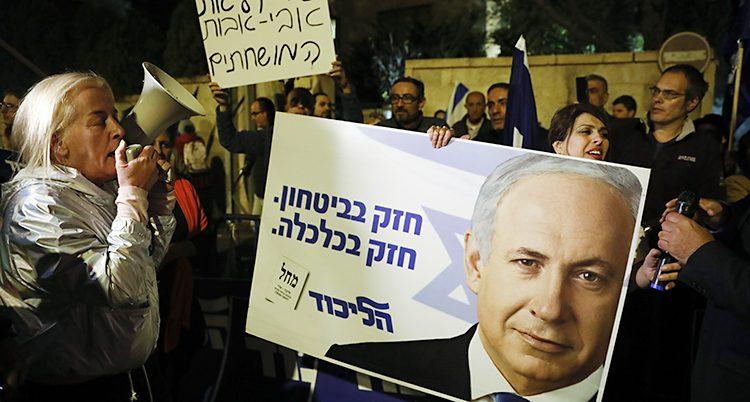 En grupp människor har samlats på en gata. De ropar saker och har plakat. De vill visa sitt stöd till politikern Benjamin Netanyahu.
