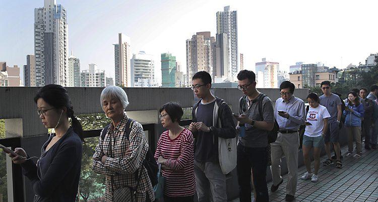 Det är en lång kö och i bakgrunden syns skyskrapor