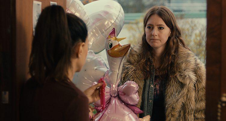 Niki står med färgglada ballonger i dörren hos sin kompis