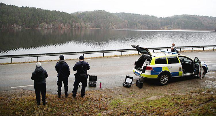 Poliser står vid en väg. Bredvid vägen syns en siö och en polisbil. De styr en drönare.
