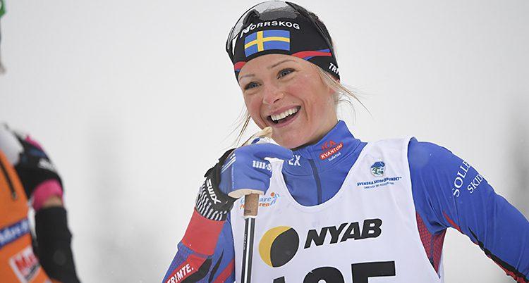 Närbild på Frida som skrattar. Hon har en mössa med svensk flagga och tävlingsdräkt och nummerlapp.