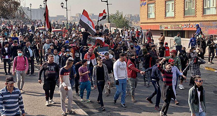 En grupp människor med flaggor följer en kista.
