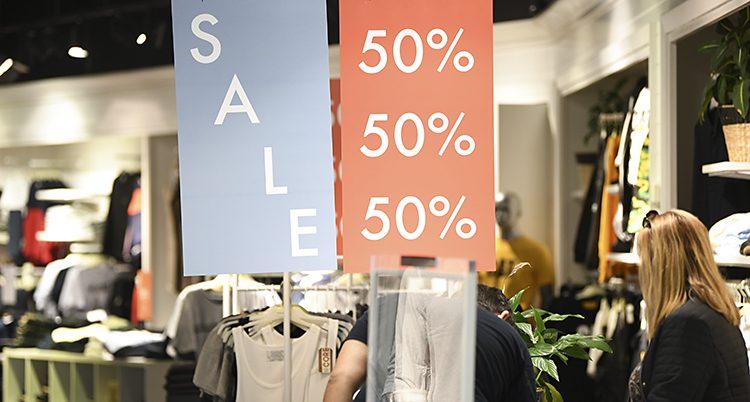 Två skyltar i en affär som det står sale på och 50 procent.