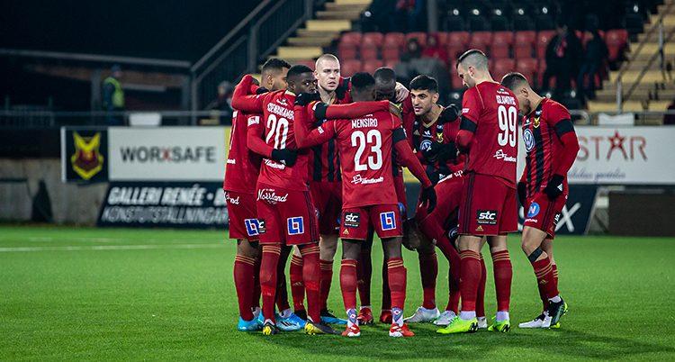 Bilden visar en fotbollsplan. På planen står en grupp spelare i ring och pratar med varandra. De har röda tröjor och röda shorts.