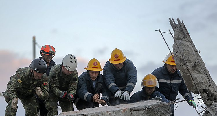 Räddningsarbetare försöker lyfta delar av ett hus som har blivit förstört.