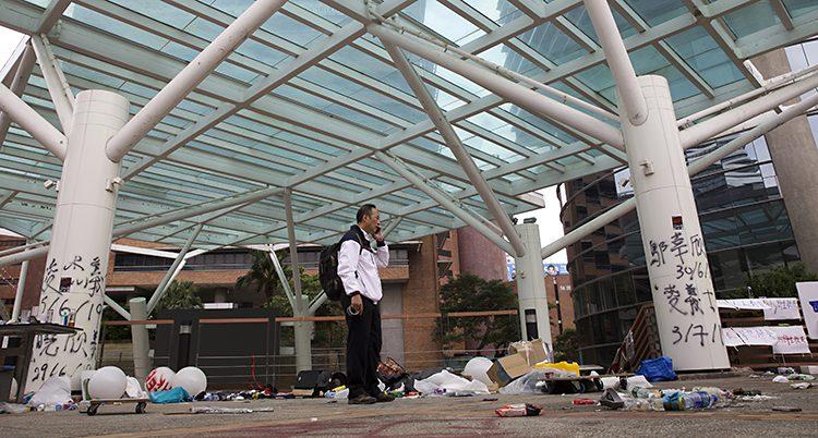 En man går omkring på ett område på ett universitet. Han står under ett glastak som hålls uppe av pelare. Runt om honom ligger en massa skräp.