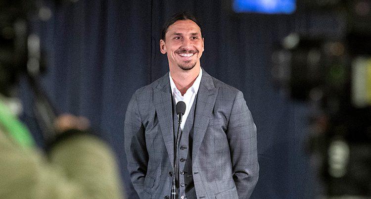 Fotbollsspelaren Zlatan Ibrahimovic står på en scen och pratar i en mikrofon. Han ler mot publiken. Han har på sig en grå kostym och vit skjorta.
