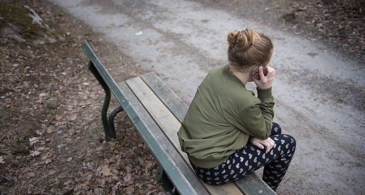 Ryggen på ett barn som sitter på en parkbänk o pratar i telefon.