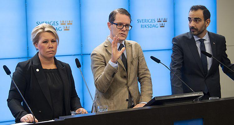 Tre politiker står bredvid varandra. De är i ett rum i riksdagen. De pratar för journalister.