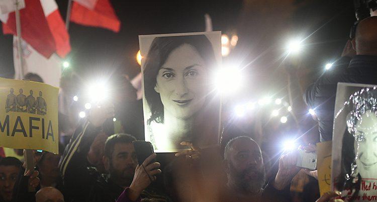 Människor håller plakat med bild på journalisten.