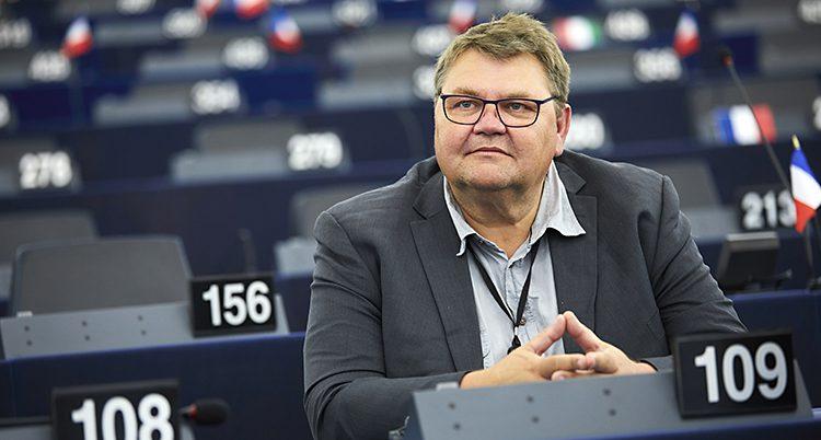 En man sitter i EUs riksdag. Det är en stor sal och varje plats har en siffra. Mannen har glasögon, skjorta och kavaj.