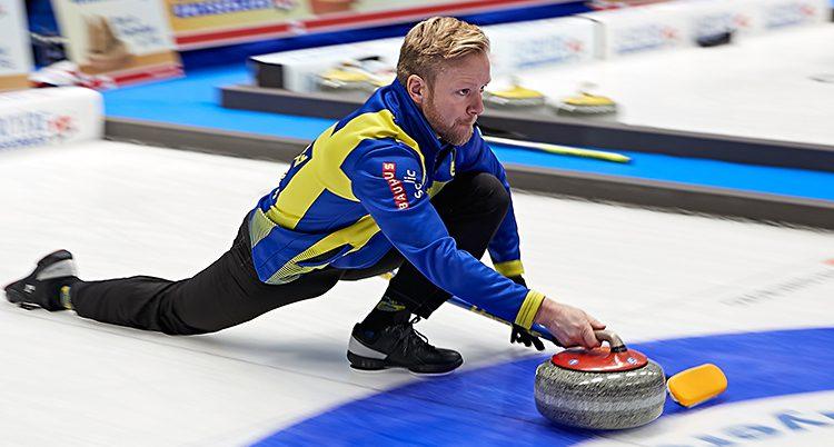 Niklas Edin glider med ett knä i isen och skickar väg en sten.