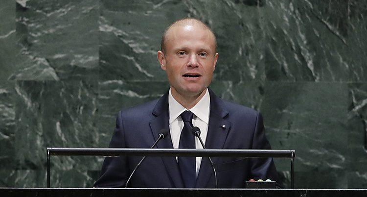 En skallig man står och pratar i mikrofon
