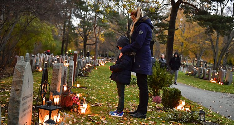 En kvinna och ett barn står vid en grav. Många ljus är tända på gravarna runt dem.