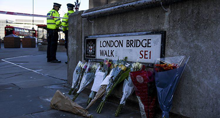 Några buketter med blommor står lutade mot en pelare av sten. I bakgrunden syns poliser