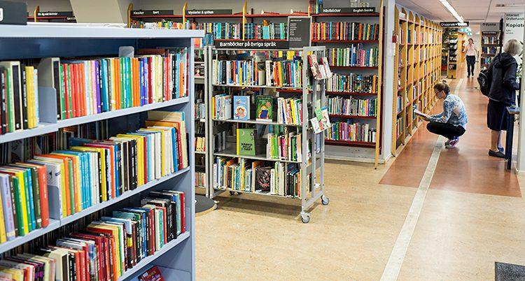 Flera hyllor med böcker på ett bibliotek.