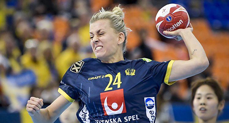 Bilden är från en match i handboll. Spelaren Nathalie Hagman laddar för ett skott. Hon har bollen i handen. Hon har blont hår som är uppsatt. Hennes tröja är blå med gula siffror.