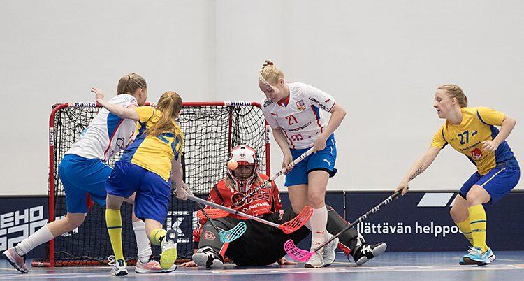 Sveriges damer spelar en match i innebandy mot Tjeckien. Två spelare från varje lag kämpar om bollen framför en av målvakterna.