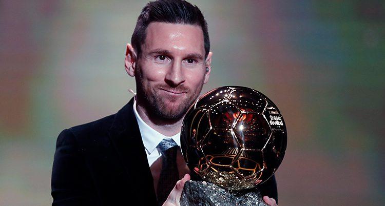 Fotbollsspelaren Lionel Messi står på en scen. Han har kostym. Han håller fram ett pris som ser ut som en fotboll. Han har kort mörkt hår.