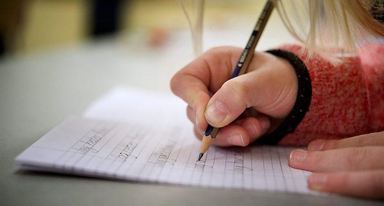 En hand håller en penna och skriver på ett papper.