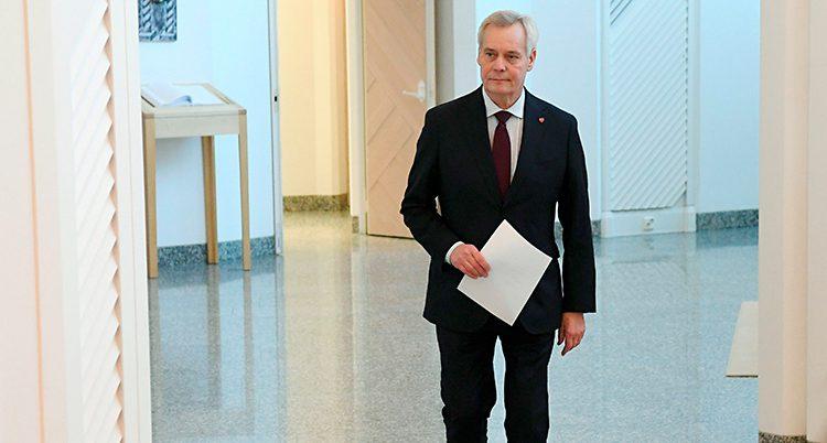 Finlands statsminister Antti Rinne går med ett papper i handen. Han har kostym och grått hår.