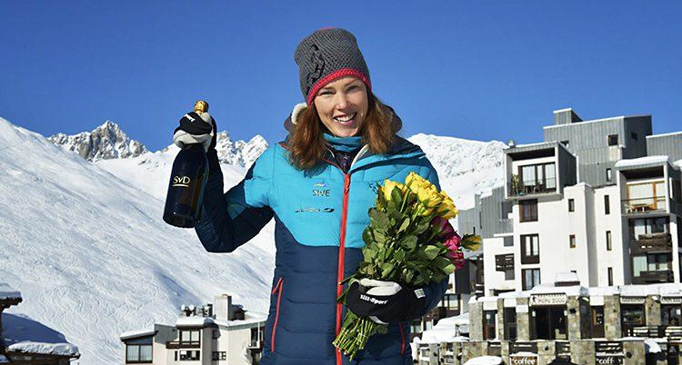 Tove Alexandersson står med en flaska champagne och en bukett med blommor. Hon står utomhus i de franska Alperna. I bakgrunden syns fjäll med snö.