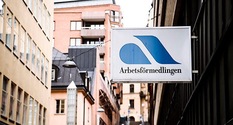 Bilden är tagen på en gata i en stad. Man ser höga hus på båda sidorna av gatan. På en av väggarna sitter en skylt där det står Arbetsförmedlingen. Skylten har en blå symbol.