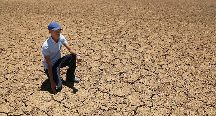 En man sitter på brun, torr mark
