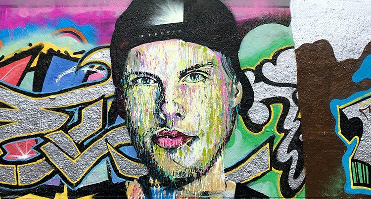 En bild målad med sprejfärg som visar artistens ansikte