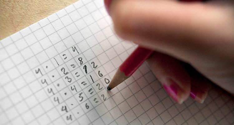 En elev sitter och räknar multiplikation.