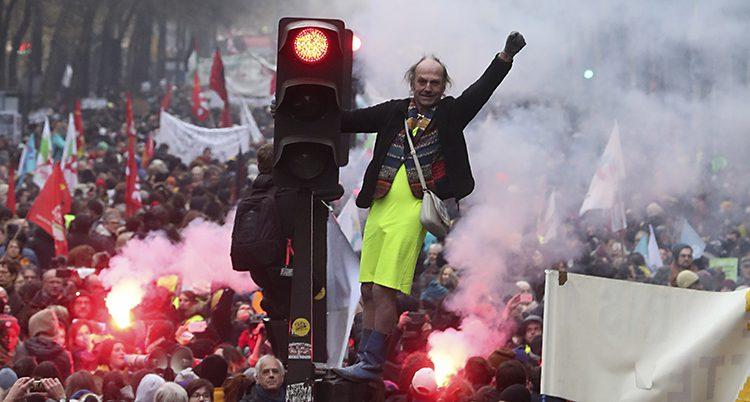 En man har klättrat upp på ett rödljus. Bakom syns ett långt demonstrationståg