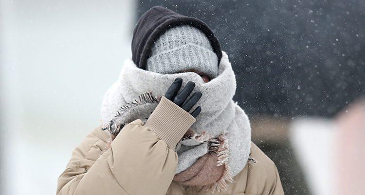 En människar döljer hela ansiktet i mössa och halsduk. Det verkar vara mycket kallt ute
