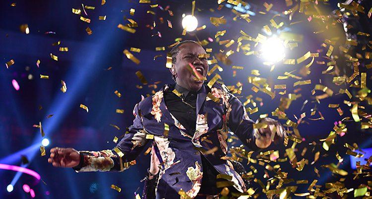 Tusse skriker av glädje och de ramlar guld-konfetti över honom