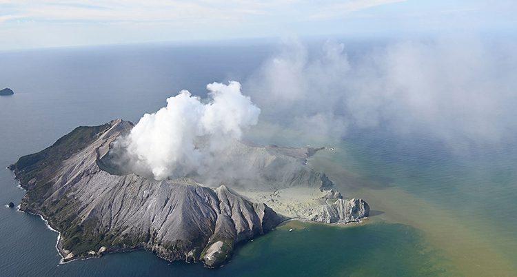 En flygbild över ön. Den är så luten att bara vulkanen får plats. Det ryker från vulkanen