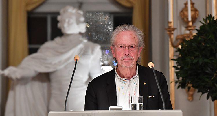 Han står framför en vit staty och talar i mikrofon