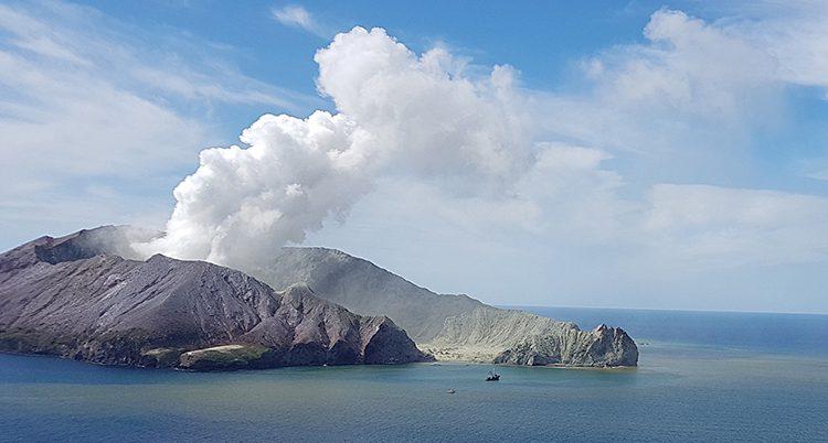 Massor av rök kommer från vulkanen som ligger ute på en ö.