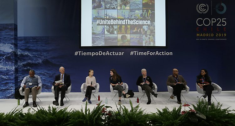 En scen med flera personer sittande i stolar. Greta Thunberg är en av dem.