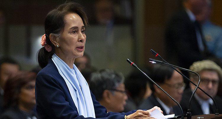 Aung San Suu Kyi står i en sal i en domstol och pratar i en mikrofon. Hon har ett hårband i nacken och en ljusblå sjal.