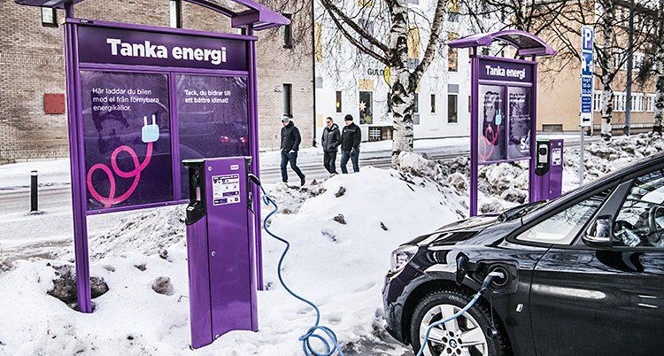 En bil laddas med el från en stolpe.
