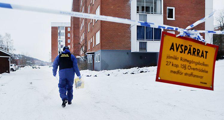 En polis går på vägen. Några höghus syns i bakgrunden. Området har spärrats av av vit och blå polistejp.