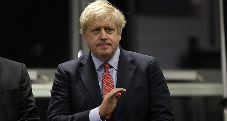 Boris Johnson har kostym och röd slips.
