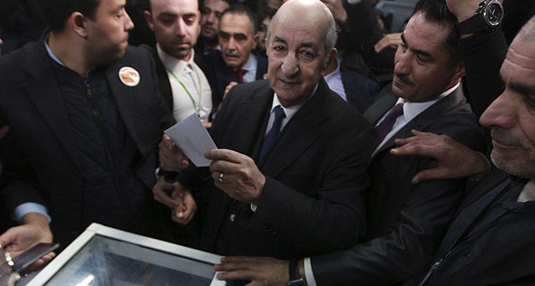 Abdelmadjid Tebboune blir ny president i Algeriet. Han håller ett röstkort i handen.
