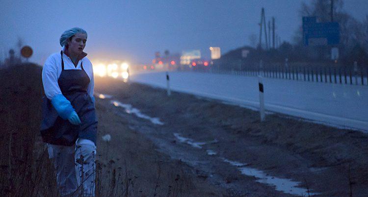 En kvinna går i vita jobbkläder längs en mörk väg